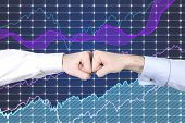 image of bump  - Businessmen fist bump with stock graphics on background - JPG