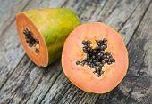 stock photo of papaya  - two halves of tropical papaya fruit on wood - JPG