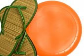 picture of frisbee  - Close up horizontal shot of green flip flops and orange frisbee or flying disc - JPG