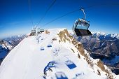 stock photo of caucus  - Ski lift chairs over the mountain peak with piste bellow on sunny winter day - JPG
