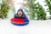pic of inflatable slide  - Funny boy with happy screaming mad face on snow tube in winter during day in the fir tree forest - JPG