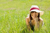 Teen Girl In Hat Is Lying At Meadow