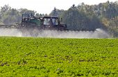 foto of fertilizer  - Tractor spray fertilize with insecticide herbicide chemicals in agriculture field and evening sunlight - JPG