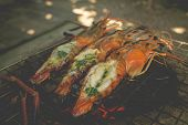 stock photo of flame-grilled  - Grilled river prawns with butter and herb on flaming grill - JPG