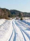 pic of snowy-road  - snowy winter road with tire markings and blue sky - JPG