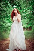 stock photo of redhead  - Beautiful redhead woman wearing white dress in the forest - JPG