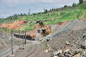 stock photo of iron ore  - Excavator loading iron ore to the train on the opencast mining site - JPG