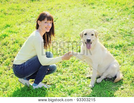 Happy Owner Woman And Labrador Retriever Dog Trains On The Grass In Summer Day