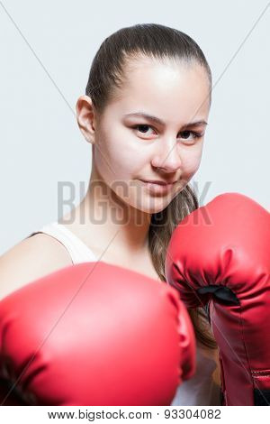 Beautiful young girl in red boxing gloves