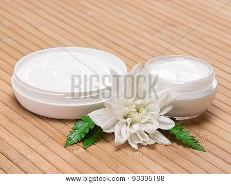 Open Jars Of Cream With White Flower And Fern Leaves