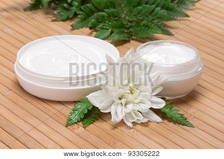 Jars Of Cream With White Flower And Fern Leaves