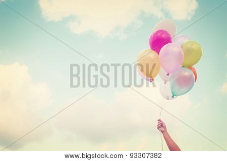 Girl hand holding multicolored balloons