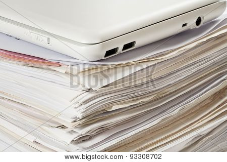 laptop computer on pile of documents