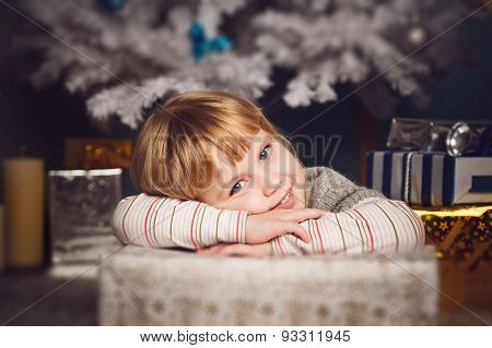 Little Girl Lying On Big Present Near The Christmas Tree