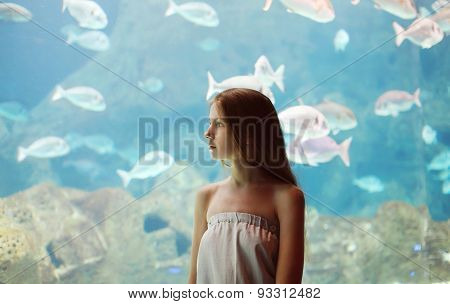 Woman In The Aquarium Looking Through The Glass On The Fishes