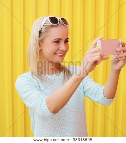 Fashion, Technology And People Concept - Happy Smiling Pretty Girl Makes Self-portrait On The Smartp