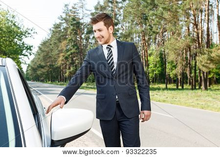 Businessman opening door of car