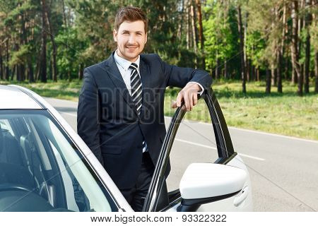 Businessman standing near opened car