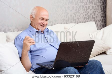 Happy old man sitting with computer