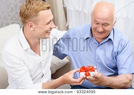 Grandfather and grandson with little present