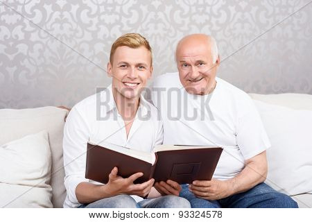 Grandfather and grandson sitting with album