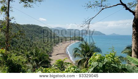 Tropical Beach Surrounded By Foliage And Mountains