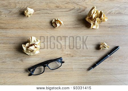 Crumpled Paper Balls With Eye Glasses And Pen On Wood Desk