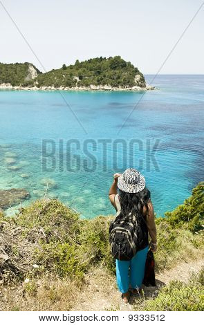 Female backpacker admiring the view in Paxos Greece.