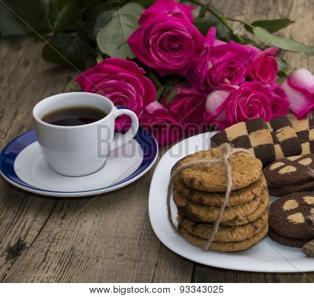 Cup Of Coffee And Cookies On A Plate With A Bouquet Of Roses