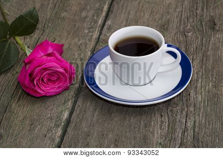 Cup Of Coffee On An Old Table And Nearby A Rose