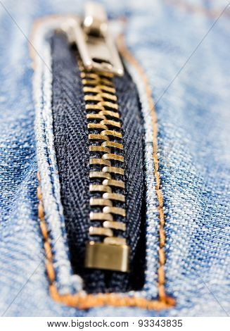 Metal Zipper On Denim Background.