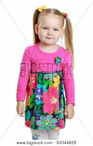 Portrait of a little blonde girl with funny pigtails on her head