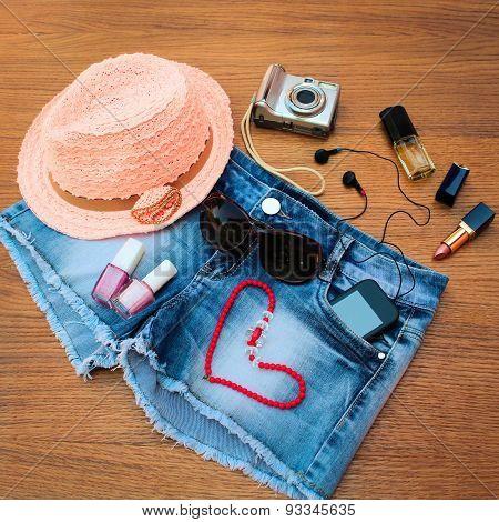 Summer women's accessories: red sunglasses, beads, denim shorts, mobile phone, headphones, a sun hat