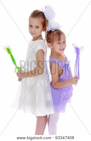 Two elegant little girls in beautiful dresses holding a magic wa