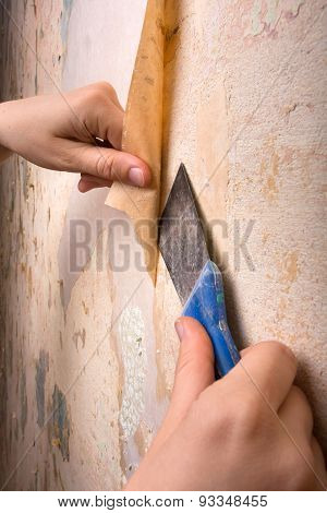 Hands Scraping Off Old Wallpaper With Spatula