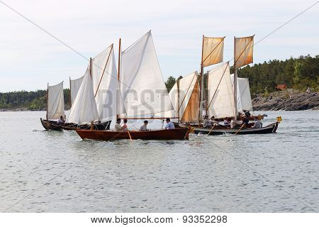 Group Of Small, Old Sailing Ships Rowing Rapidly