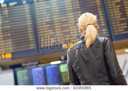 Female traveller checking flight departures board.