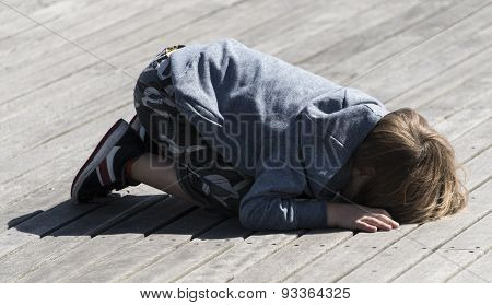 Boy On Peering Through Slats In Wooden Planks