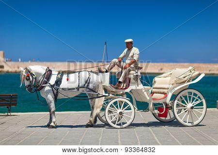 Coachman with a beautiful white horse. Crete, Greece.