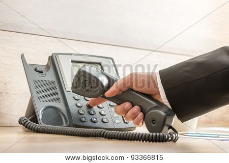 Closeup Of A Hand In A Formal Elegant Suit Dialing A Telephone Number