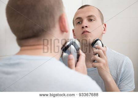 Man Shaving With Electric Razor In Bathroom