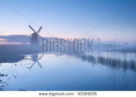 Dutch Windmill In Dense Sunrise Mist