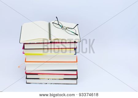 Open blank notebook on the stack of colorful books.