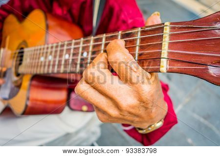 Close up to hands of an indigenous man playing guitar in the central plaza of Armenia, Colombia