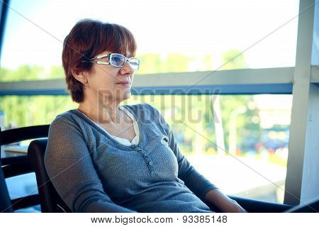 Woman sitting in the airport cafe and waiting for departure.