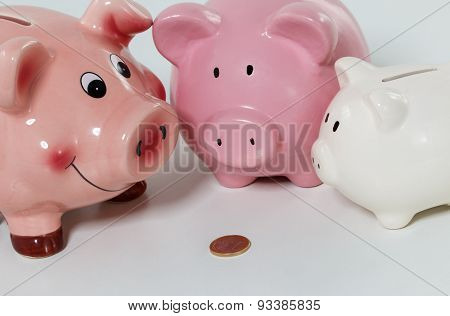 Three Piggybanks On Table