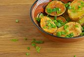 picture of baked potato  - Baked potatoes with herbs on wooden table. ** Note: Shallow depth of field - JPG