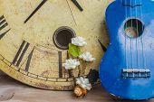 stock photo of ukulele  - Ukulele and a watch at the walls - JPG
