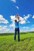 stock photo of throw up  - Father throws daughter up in the air in the summer park - JPG