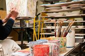 image of pottery  - Work table of a pottery decorator of Caltagirone with different color containers and paintbrushes  - JPG